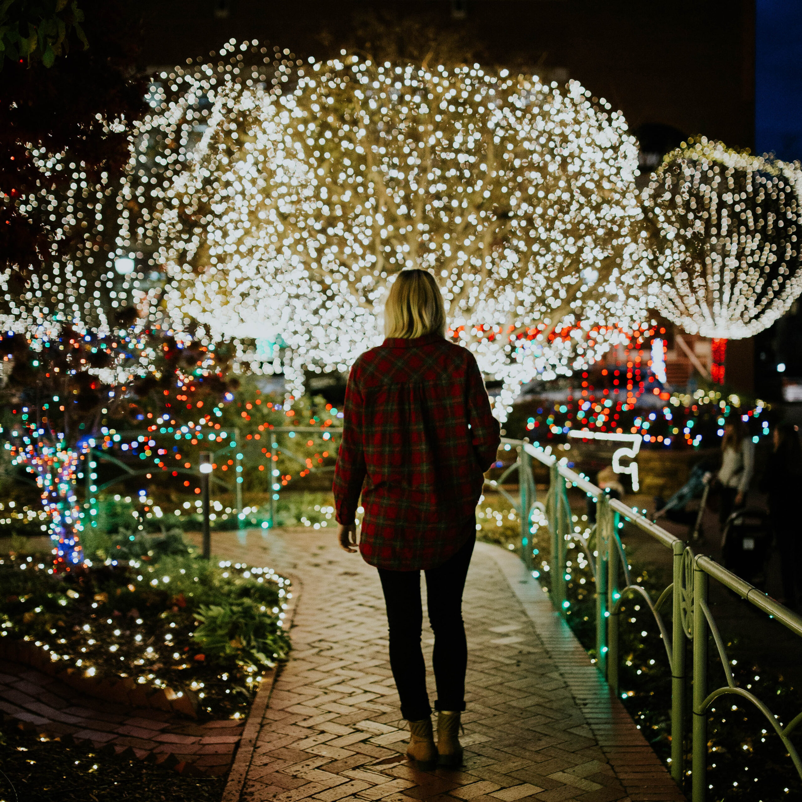 woman walking through area decorated with holiday lights